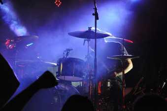 Drummer playing on a poorly lit stage