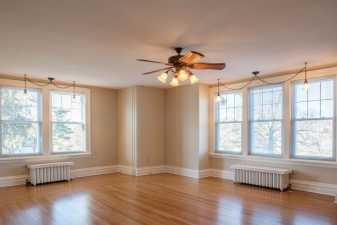 an empty living room with an overhead ceilng fan whose lights are lit