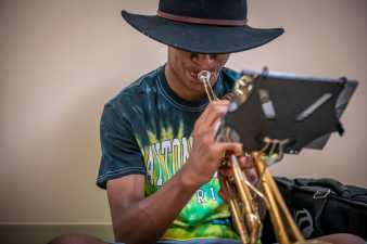man playing the trumpet, his bucket hat covers his eyes
