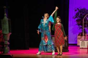 man and woman in costume on stage with their hands linked and raised in the air
