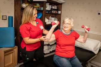 a physical therapist working with an elderly woman on lifting weights