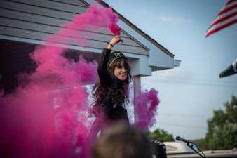 a woman smiling and holding a purple smoke grenade