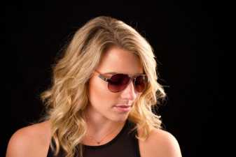 blond woman in sunglasses looking down with her eyes closed