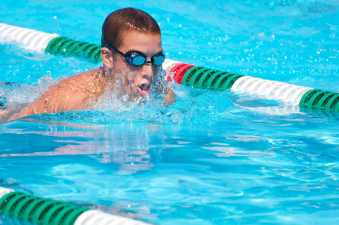 young man in goggles swimming in his lane