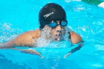 young man in a swimming cap taking a breath during his swimming race
