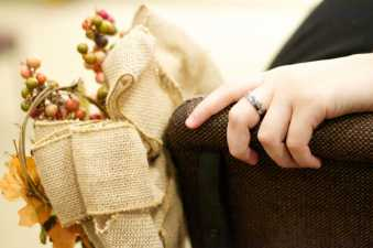 a hand with a wedding band and fall wedding decorations