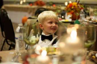 a young boy sitting at a wedding table smiling