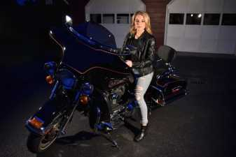 a young woman on a harley at night in her driveway