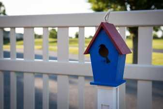 blue birdhouse sitting on a fence