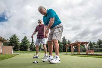 two older men practicing putting