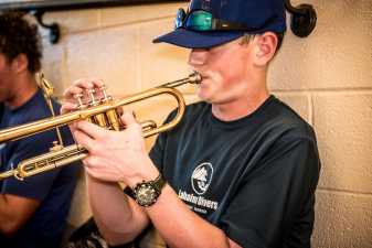 a male student practicing his trumpet