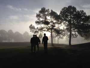 three golfers in the fog at dawn