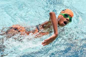 a kid in a swimming cap taking a breath during his swimming race