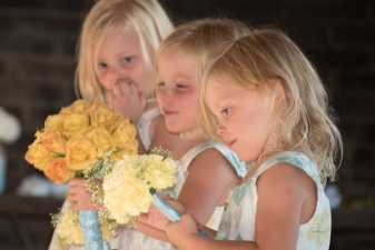 three young girls holding flowers at a wedding
